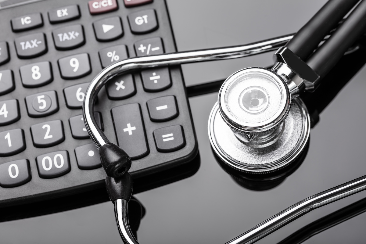 Calculator And Stethoscope On Black Background